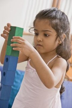 Children learn about balancing when they stack blocks.