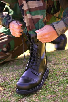 Soldier lacing up Army boot