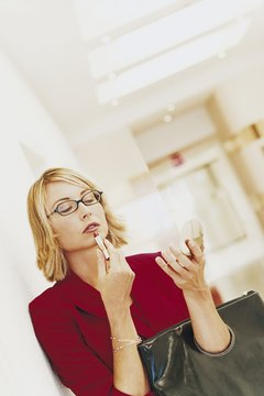 Businesswoman Looking at a Hand Mirror and Applying Lipstick in an Office Corridor
