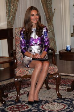 The Duchess of Cambridge sits with her legs together in a short dress.
