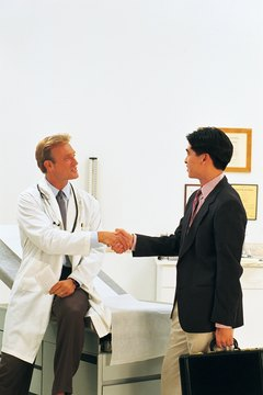 Doctor and businessman shaking hands in clinic