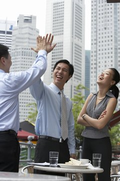 Businesspeople giving high five at outdoors cafe