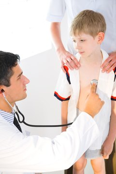 Doctor listening to boy's heartbeat with stethoscope