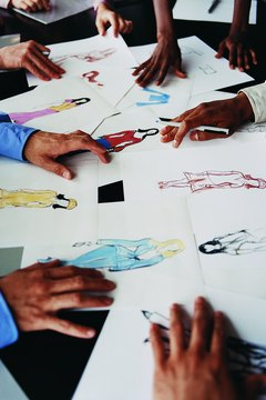 Close up of Hands on a Table With a Fashion Designer's Drawings
