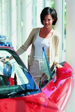 Woman looking at red car in showroom