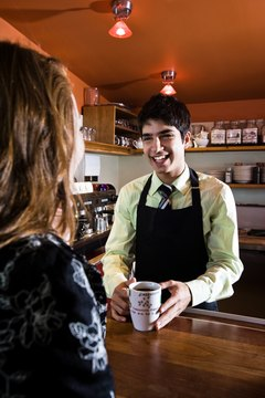 Smiling coffeehouse barista serving customer