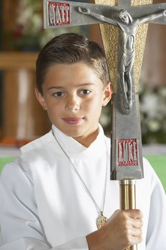 An altar boy carries a large crucifix mounted on a staff as part of a Mass procession.