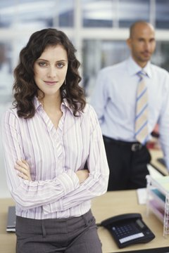 Businesswoman and man by desk in office, portrait
