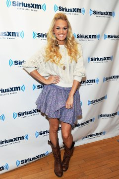 Singer Carrie Underwood is a poster child for country-chic style in chunky boots and a cotton floral miniskirt.