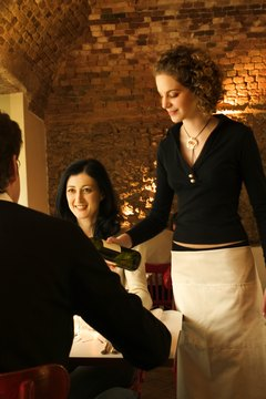 Waitress pouring wine for couple in restaurant