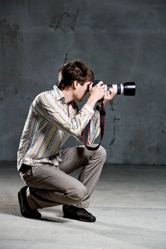 Studio shot of crouching photographer