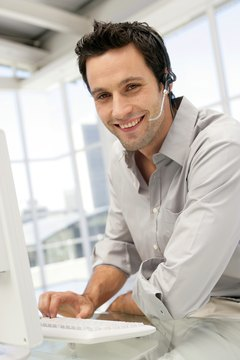 Businessman wearing headset and using computer