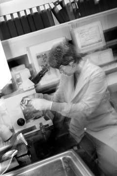 Female technician using microscope