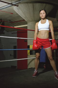 Lifting weights and jumping rope during your boxing workout build muscles and burn calories.