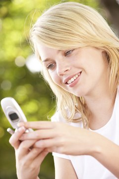 Teenage girl dialing phone number into cellular phone
