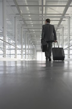 Businessman in airport, pulling luggage, rear view