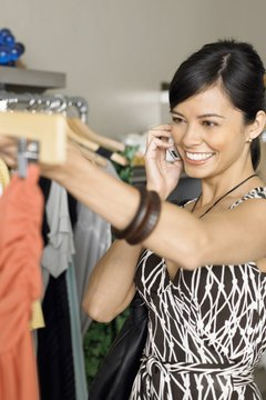 Young woman shopping in boutique while on mobile phone