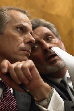 Mature man whispering to colleague in pew, close-up