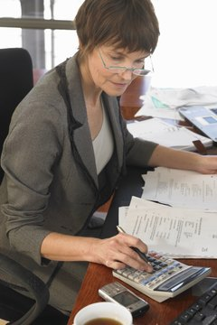 Businesswoman sitting at desk with documents using calculator
