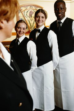 Manager looking at restaurant staff, focus on staff