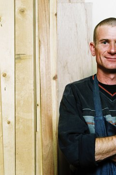 portrait of a carpenter standing with wooden planks