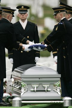 U.S. Army honor guard members fold the flag covering a funeral casket at Arlington National Cemetery.