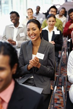 group of business executives clapping at a seminar