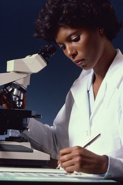 Lab Technician With Microscope Taking Notes