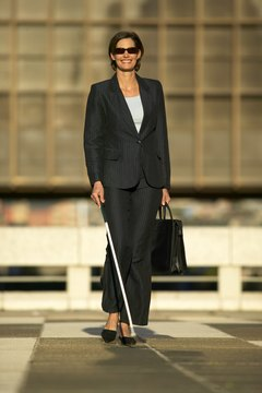 blind businesswoman walking with the aid of a white stick