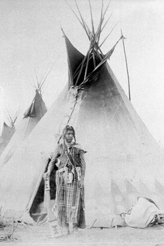 This Blackfoot Native American stands before a teepee.
