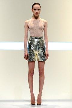 A model at Matheiu Mirano sports a beige top with a metallic skirt for an ultra-chic ensemble.