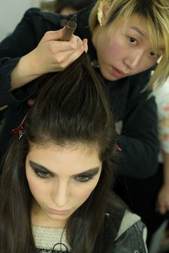 A hairstylist crafts a poof on a model backstage during Hong Kong Fashion week in January 2014.