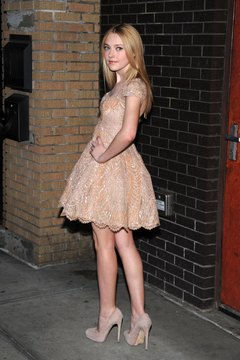 Actress Dakota Fanning pairs her embellished dress with nude heels.