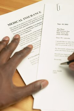 Close-up of hands signing an insurance document