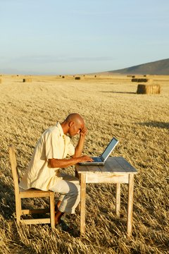 Man at desk with laptop in field