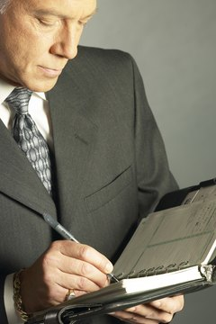 Businessman writing in appointment book