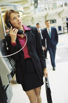 Businesswoman talking on pay phone