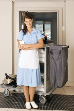 Maid with cleaning supplies on cart