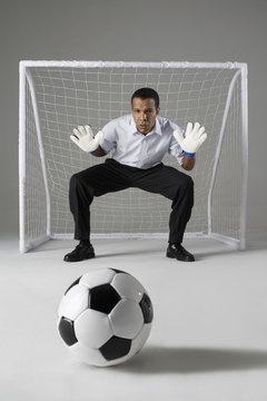 Businessman playing goalkeeper, ready to block the ball, studio shot