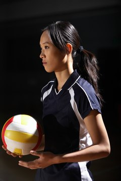 Young woman holding volleyball, side view