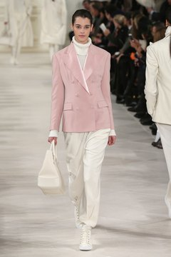 A model rocks a dusty rose blazer with an all-white ensemble on the runway during Fashion Week in New York in February 2014.