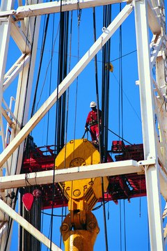 Oilfield engineers often don a hard hat and supervise the work crew.
