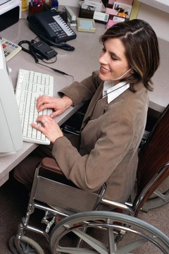 Young adult Caucasian female in a wheelchair working at a desk