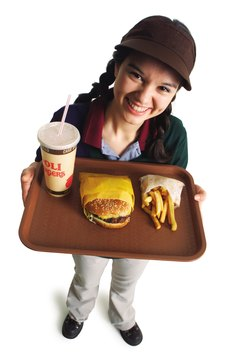 a teenage caucasian girl in a fast food uniform serves a burger and fries as she smiles and looks up at the camera