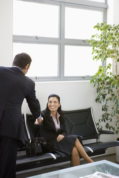 Businesswoman shaking hands with man in office lobby