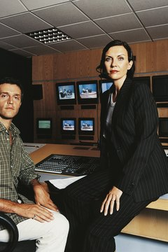 Portrait of a TV Presenter and a Producer Sitting in the Control Room of a TV Studio