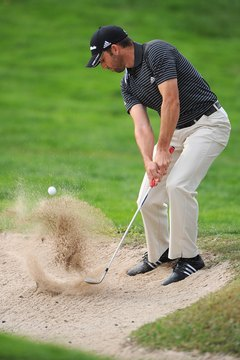 Hitting sand shots with spin will stop the ball quickly on the putting surface.
