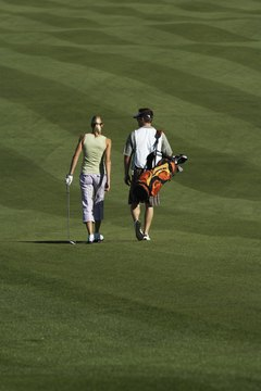A player and her caddie walk down a well-groomed fairway.
