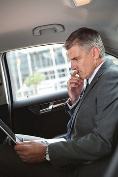 Businessman in car with laptop