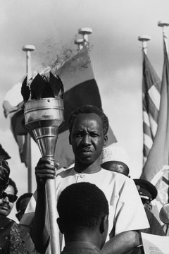 Nyerere is presented the torch of freedom by Tanzania's youths in 1966.
